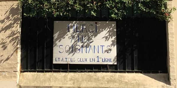 Pancarte accrochée à un portail avec le texte : Merci à nous soignats et à tous ceux en 1ère ligne
