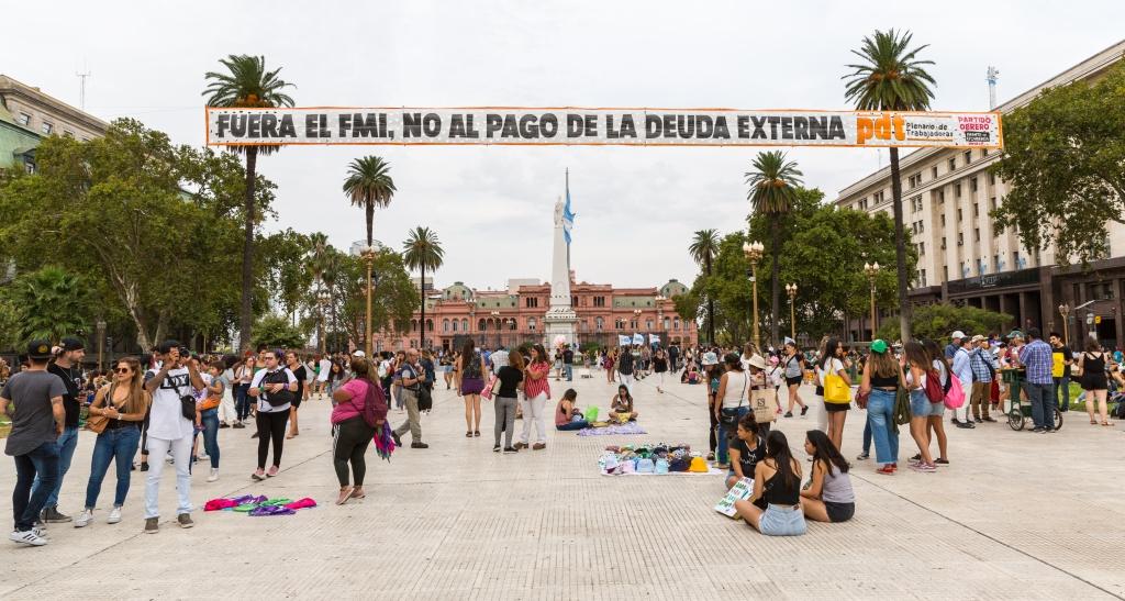 Plaza de Mayo, vaste esplanade où des gens assis attendent le début de la marche avec leurs pancartes