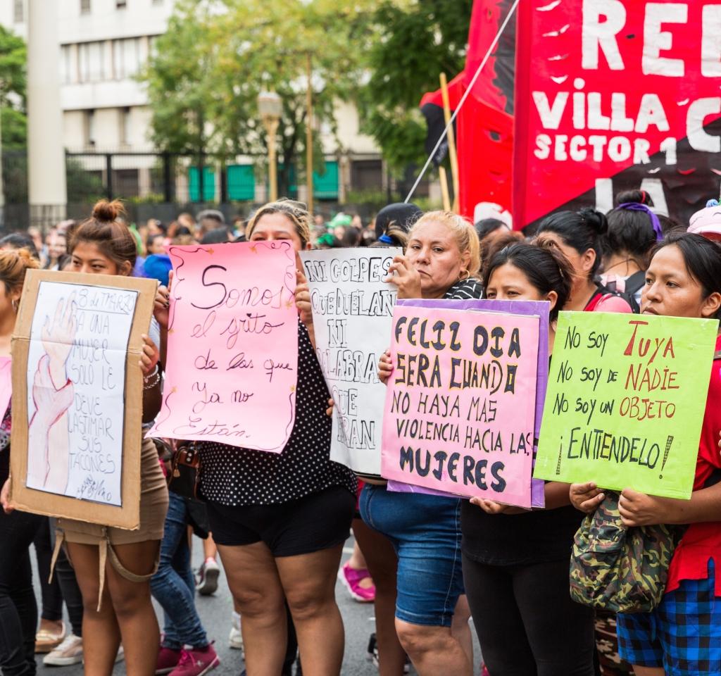 Cinq femmes d'âges divers alignées portent des pancartes.