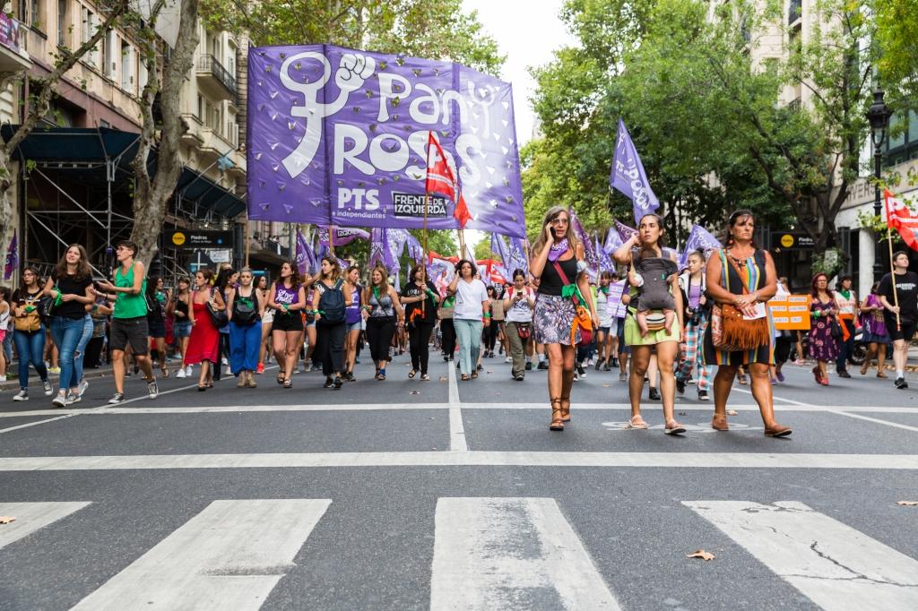 Des militantes marchent dans le cortège et portent de nombreux drapeau violet couleur du féminisme