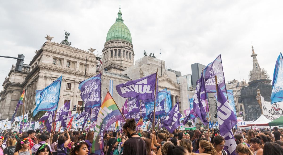 Manifestation à Buenos Aires où l'on voit une foule nombreuse avec des drapeaux violets, des femmes avec des couronnes de fleurs ou des t-shirts violets