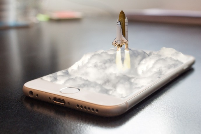 D'un écran de portable sort dans un nuage de fumée une fusée qui décolle