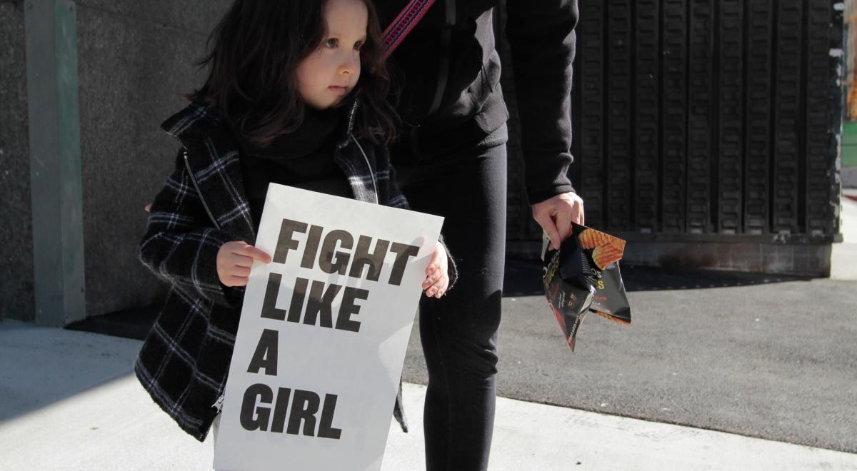 """Une femme avec un pussy hat rose pousse dans le dos une petite fille brune qui porte le panneau """"fight like a girl"""""""
