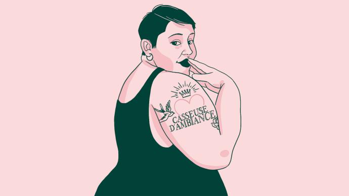 """Une femme de trois quart nous regarde la main sur la bouche un tatouage sur l'épaule avec un coeur et le texte """"Casseuse d'ambiance"""""""