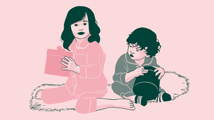 Une enfant en pyjama rose avec un cadeau rose et un garçon en pyjama vert avec un cadeau vert qui regarde le cadeau rose, les deux assis sur un tapis à poils.