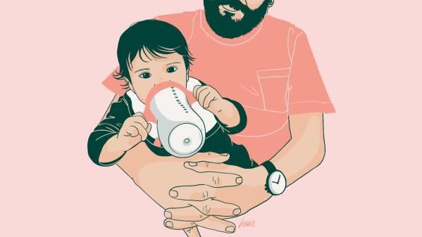 Un bébé boit un biberon dans les bras de son papa